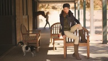 Girl sitting in barnyard.